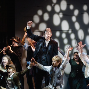 An image of our first production of Charles Dickens' 'A Christmas Carol'. The stage is full of musicians and people singing with the central character of the play holding one arm to the air in jubilation.